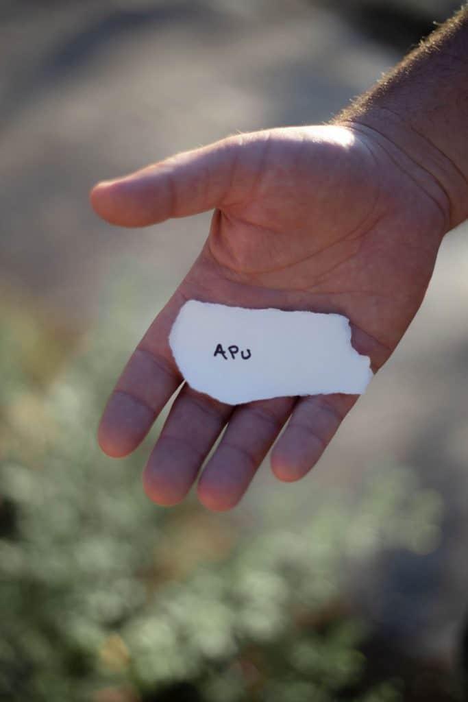 """Henkilön kädessä pieni paperipala, jossa lukee """"APU"""""""