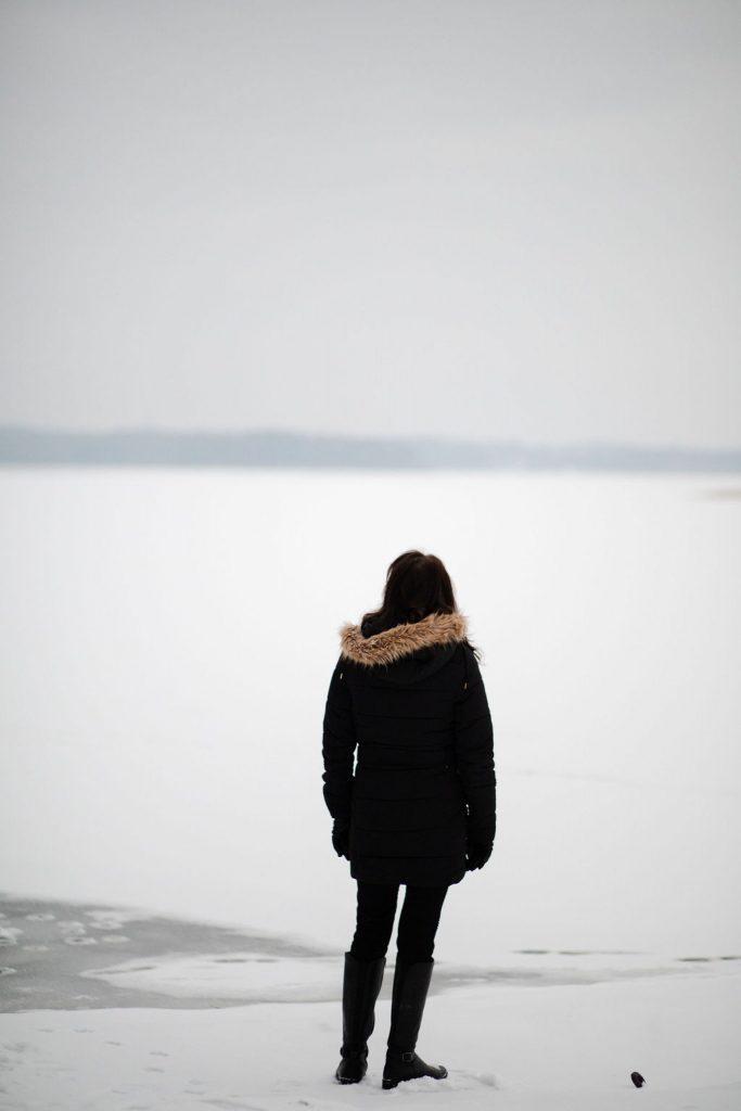 Nainen mustassa takissa, seisoo jäällä ja katsoo kauas horisontiin Saimaan rannalla. Kaukana horisontissa näkyy metsä. Nainen on peliriippuvaisen omainen.