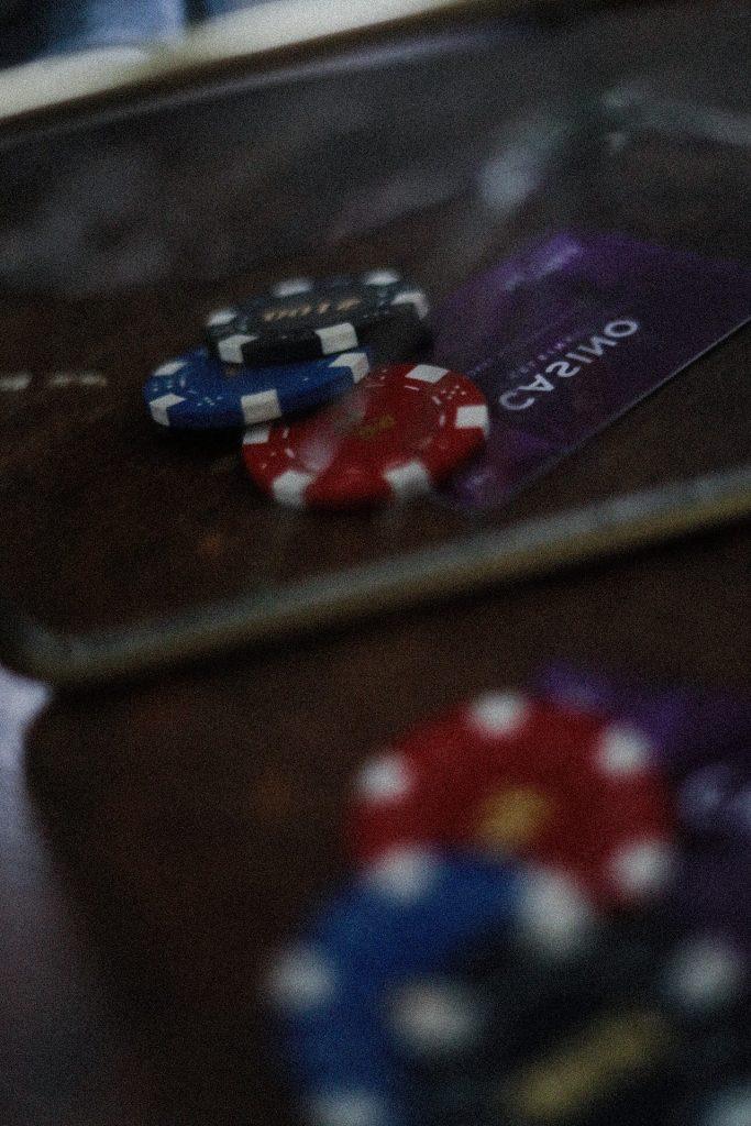 Kuvassa näkyy pelimerkkejä ja kasinokortti, jotka heijastuvat kuvan katsojalle rikkinäisestä peilistä.