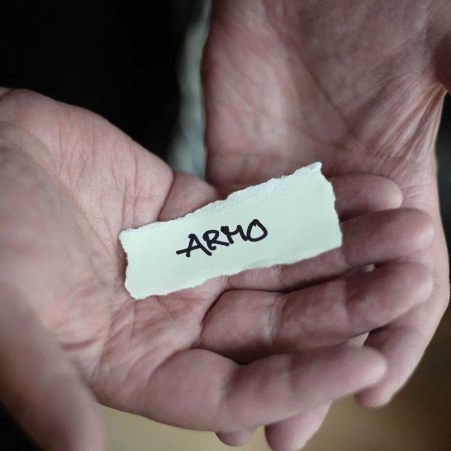 """Henkilön kädessä pieni paperipala, jossa lukee """"armo"""""""