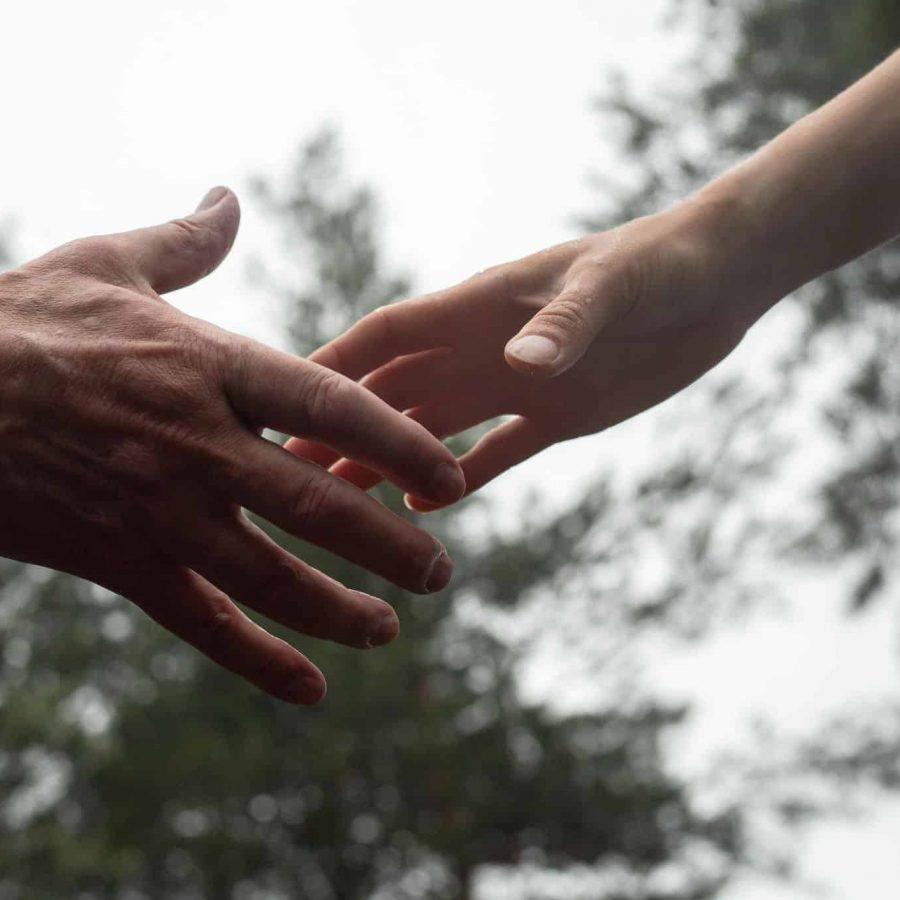 Kaksi kättä koskettavat melkein toisiaan